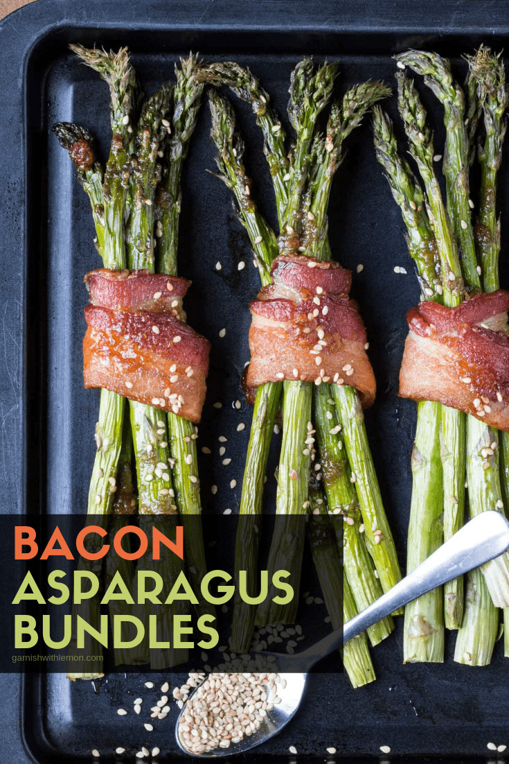 A close up of bacon wrapped asparagus on a black tray.