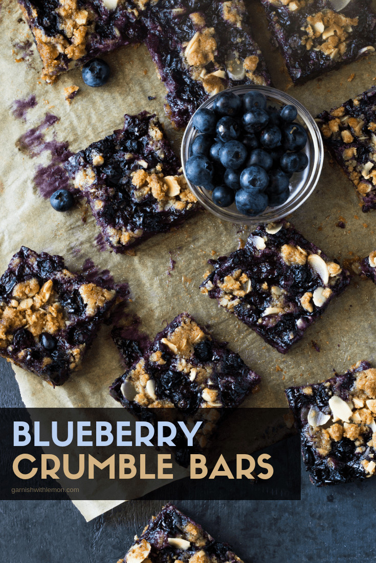 Cut Blueberry Crumble Bars on parchment paper with a small bowl of blueberries.