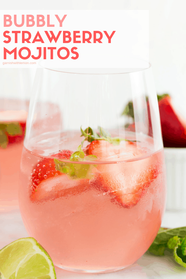 Bubbly Strawberry Mojito recipe in a low ball glass on ice garnished with fresh strawberries.