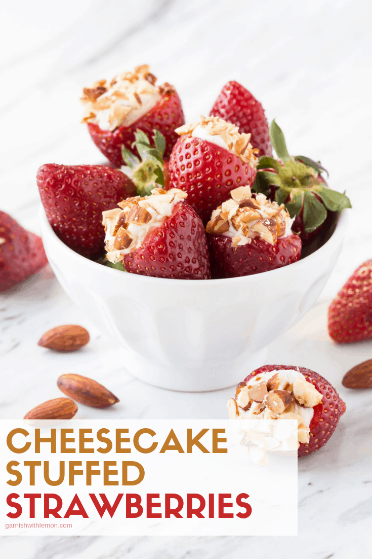 Cheesecake Stuffed Strawberries garnished with chopped almonds in a white serving bowl.
