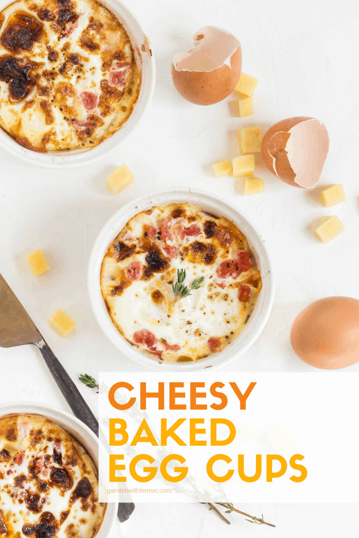 Cheesy baked egg cups in white ramekins with cheese chunks and brown eggs on side.