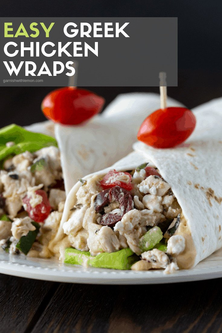 Two Greek Chicken wraps on a white plate with a grape tomato on top.