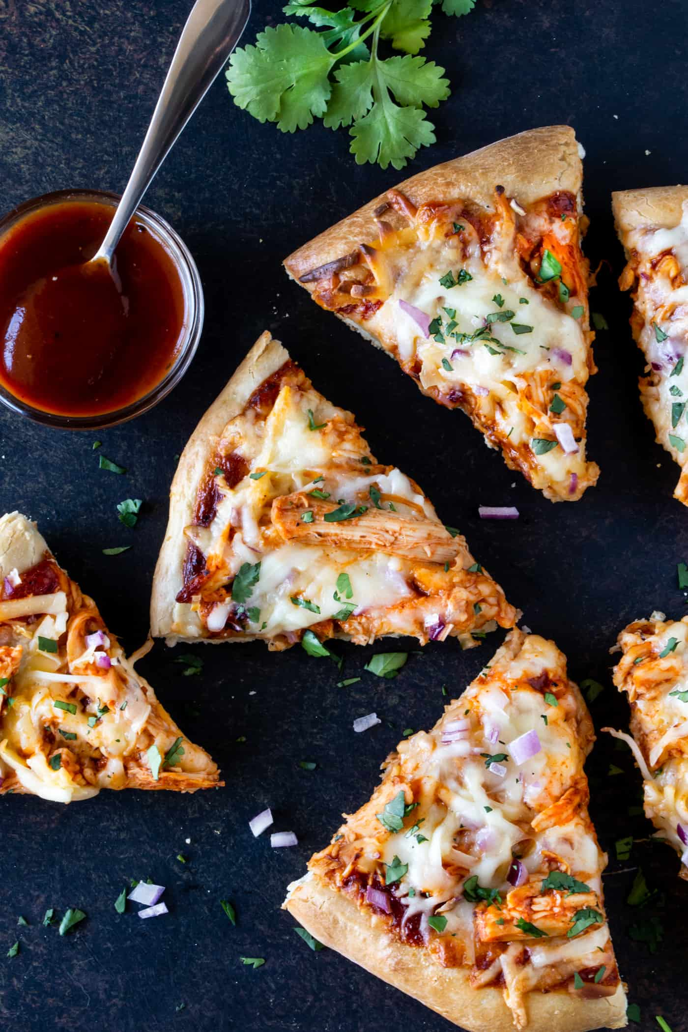 Slices of BBQ Chicken Pizza on a dark gray board. Sprinkled with fresh cilantro and garnished with extra BBQ Sauce.