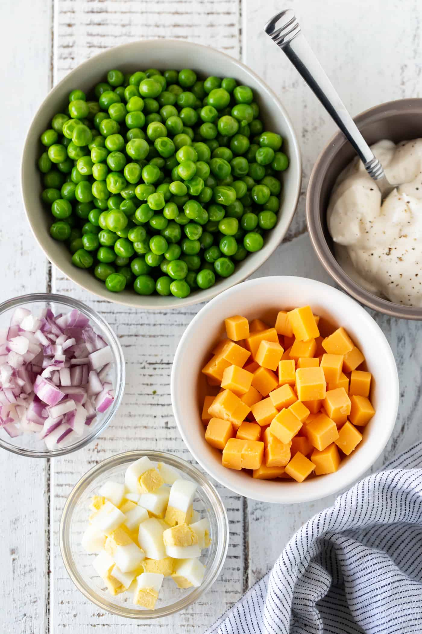 Imgredient shot of items needed for Easy pea and Cheese Salad in separate white bowls.