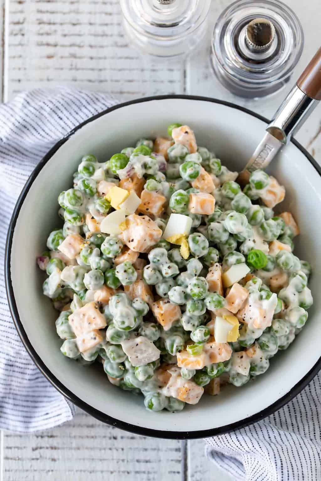 Easy Pea and Cheese Salad in a white bowl with a black rim. Garnished with fresh pepper and has a spoon for serving.