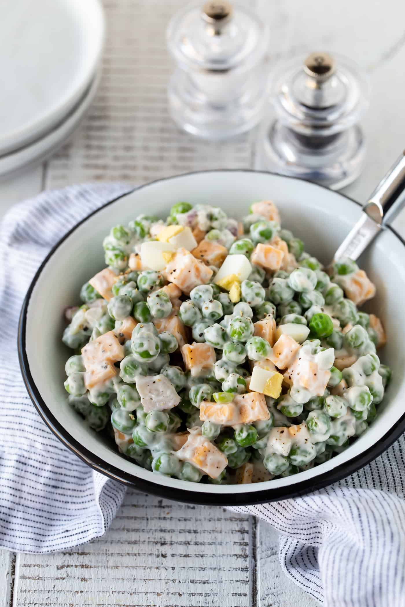 Easy Pea and Cheese Salad in a white bowl on a white background with salt and pepper shaker on the side.