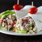 Two Greek Chicken Wraps on a white plate, with a grape tomato on a toothpick.