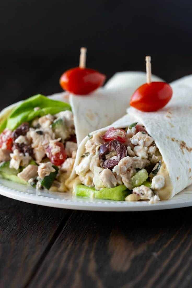 Two Greek Chicken Wraps on a white plate garnished with a grape tomato on a toothpick.