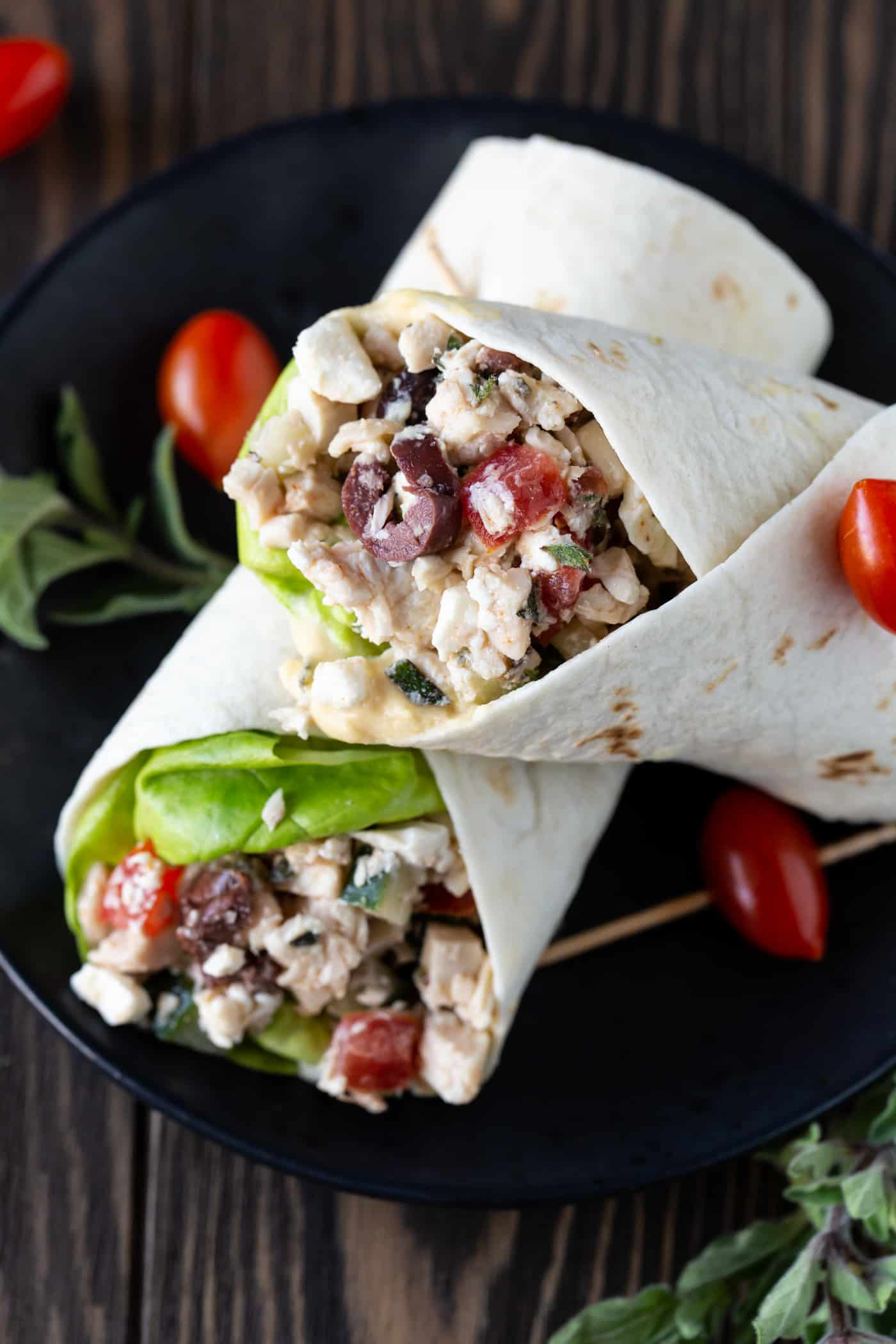 Two Greek Chicken Wraps on a plate garnished with fresh lettuce and tomatoes.