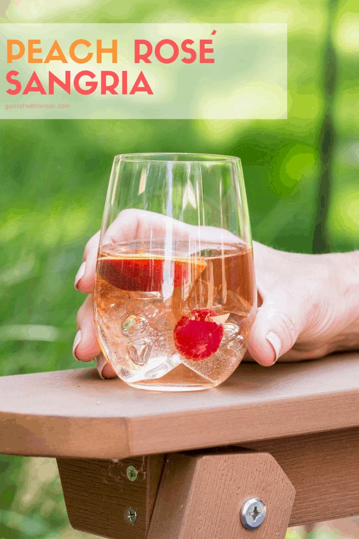 Peach Rosé Sangria in a stemless wine glass garnished with fresh raspberries and peaches.