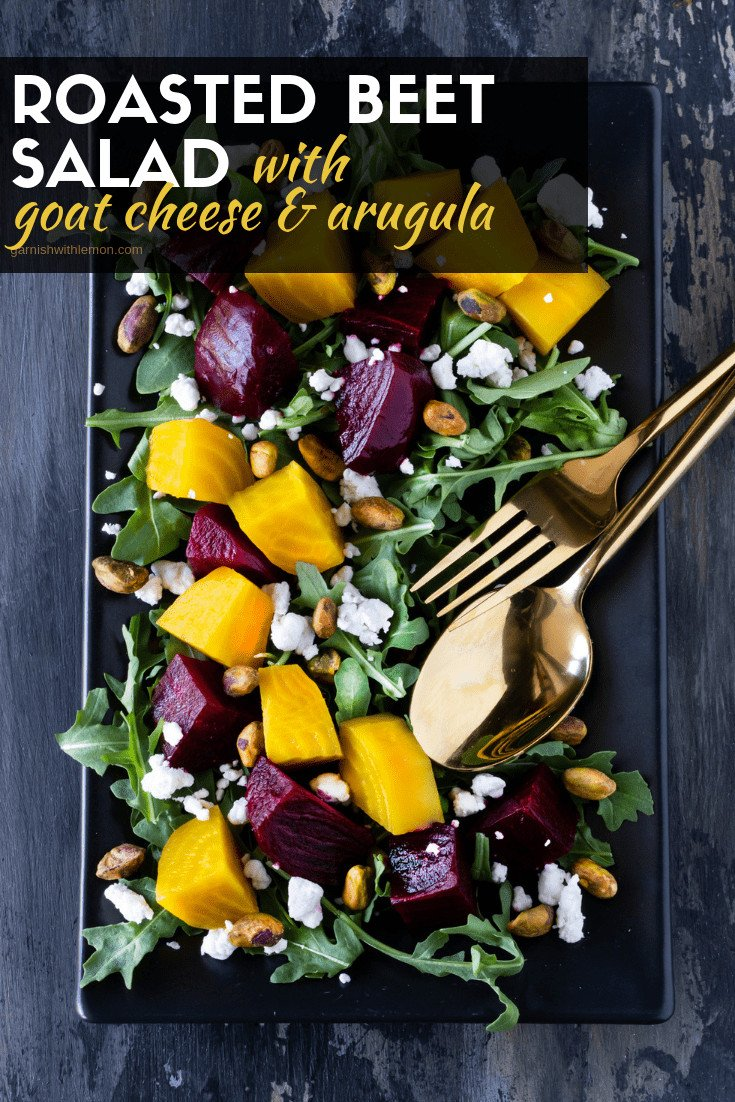 Black platter of Roasted Beet Salad with Goat Cheese, Arugula and Pistachios.