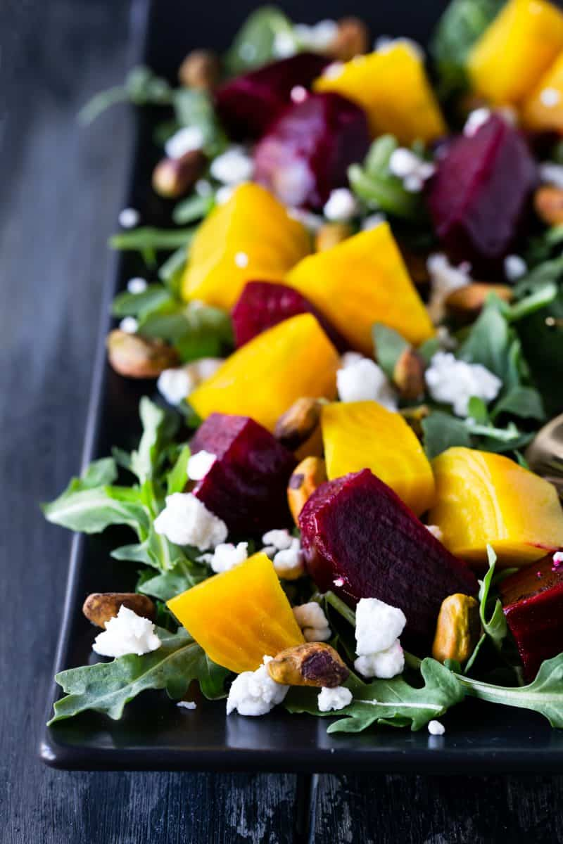 Close up of Roasted Beet Salad with Goat Cheese, Arugula and Pistachios on a black platter.