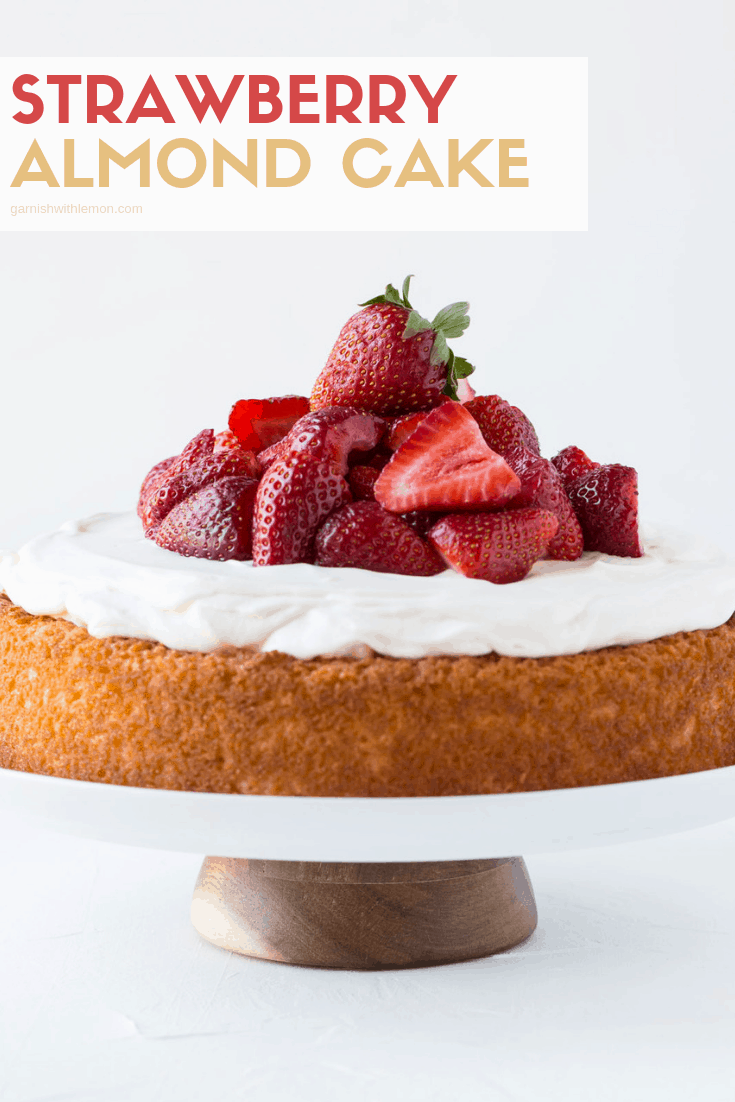 Strawberry Almond Cake topped with frosting an a pile of fresh cut strawberries.