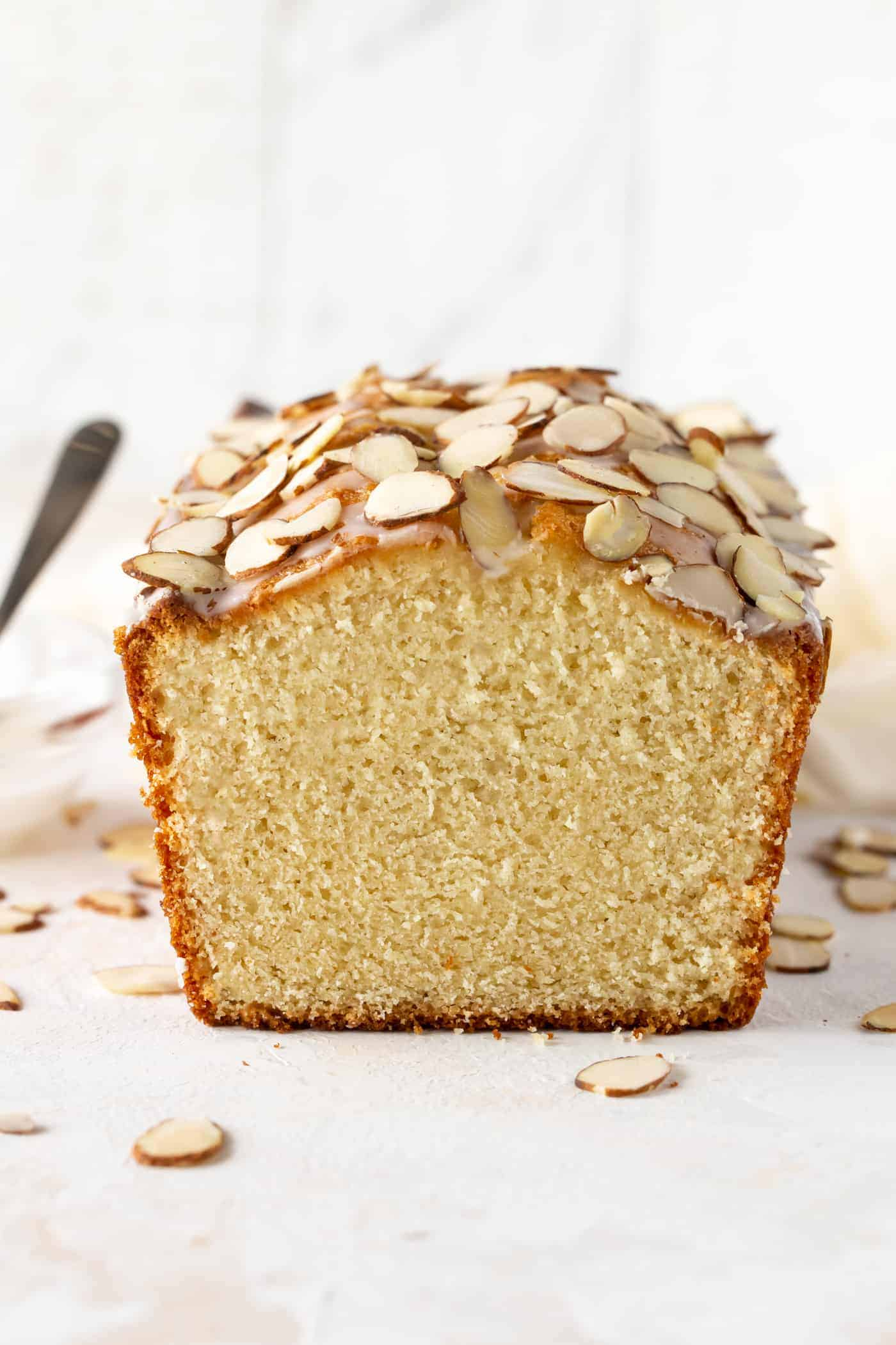 This Almond Pound Cake is drizzled with an almond glaze and sprinkled with more sliced almonds on a white board.