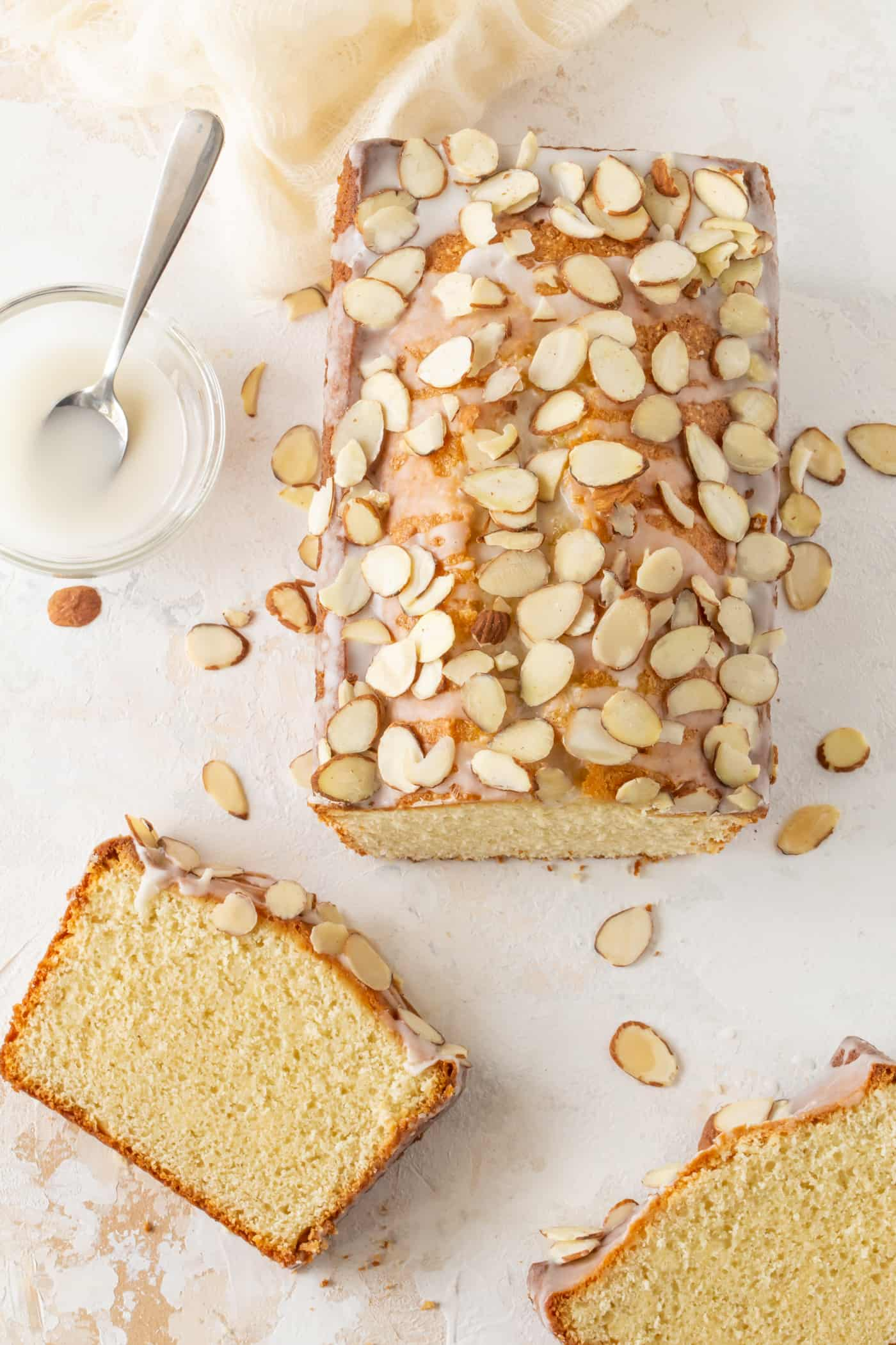 A loaf of easy Almond Pound Cake drizzled with almond glaze and sliced almonds.