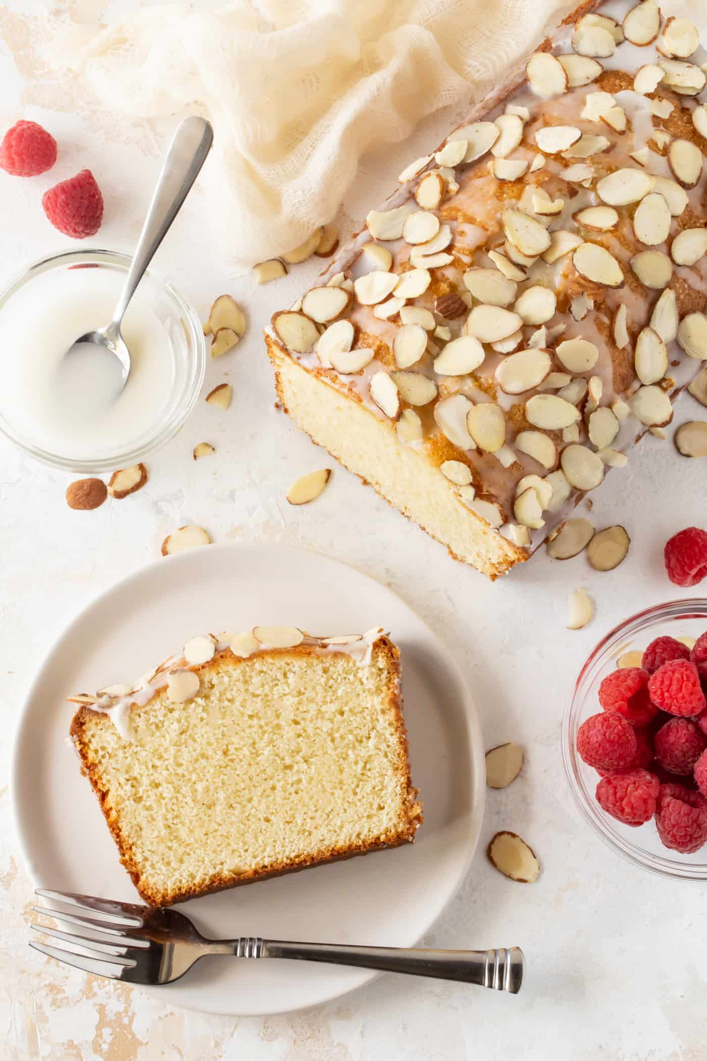 A loaf and a few slices of easy Almond Pound Cake made with almond paste. Both are drizzled with almond glaze and topped with sliced almonds.