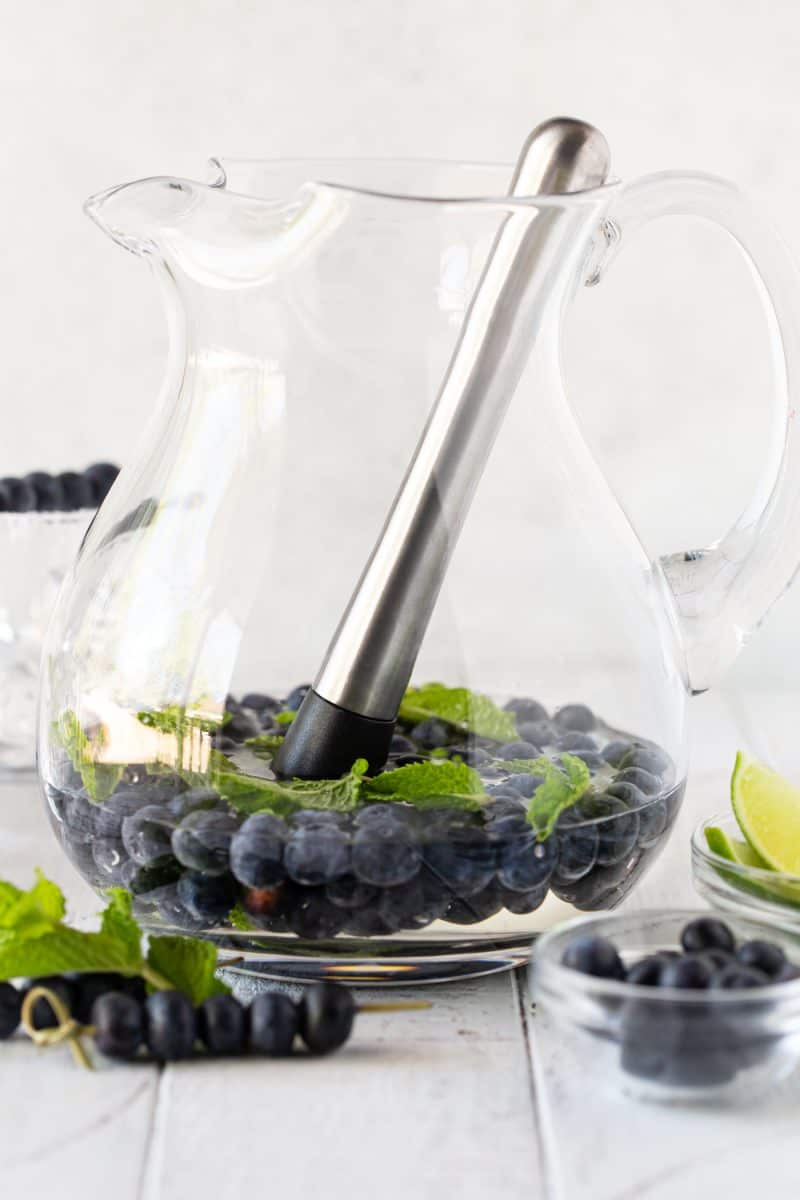 Glass pitcher filled with simple syrup, mint, fresh blueberries and a muddler.