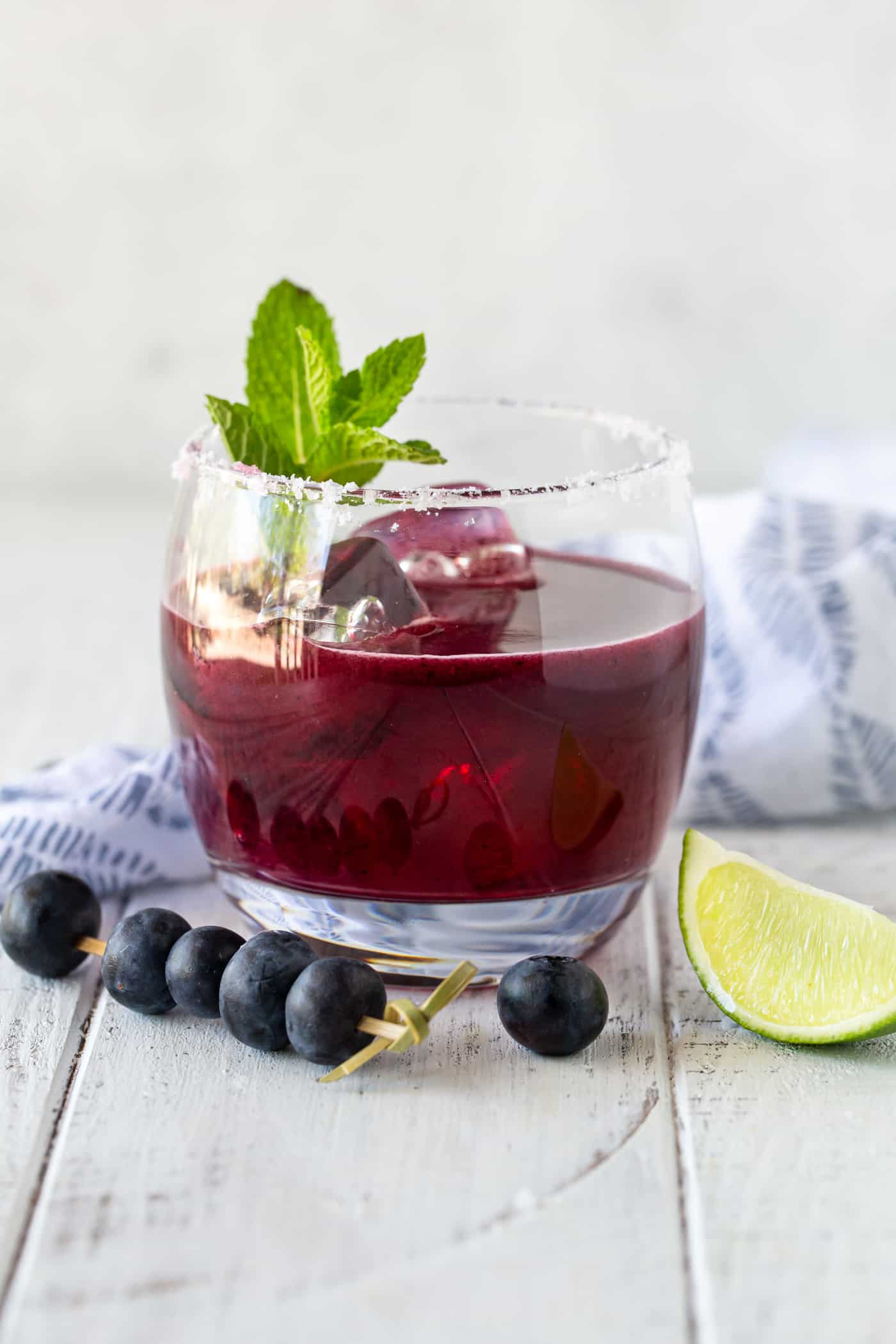Single low ball glass rimmed in salt and filled with ice a fresh blueberry margarita on a white background.