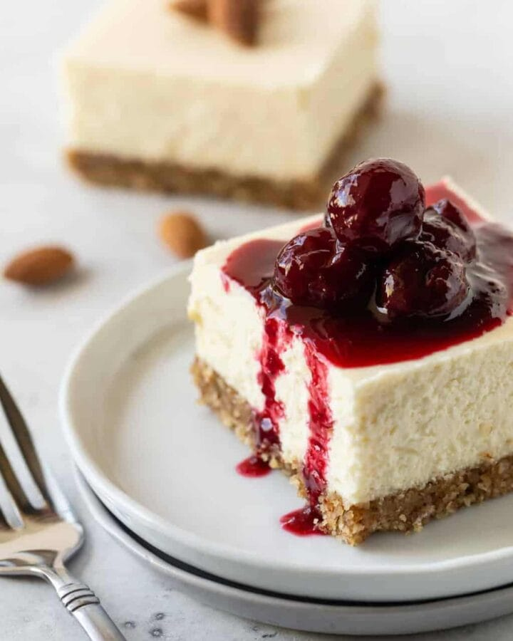 A Gluten-Free Cherry Almond Cheesecake Bar slice on a small white plate with a fork.
