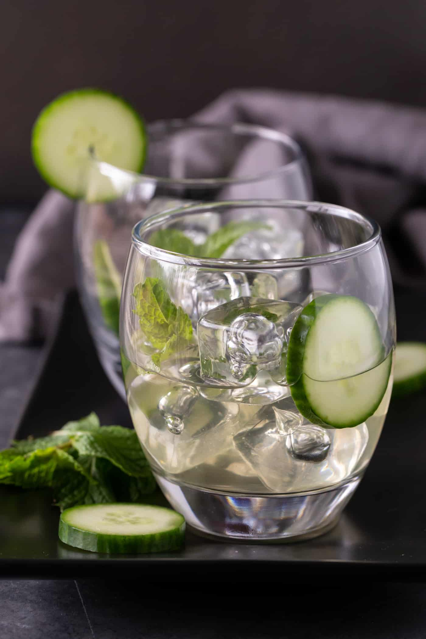 Two low ball glasses of Cucumber Melon Sangria garnished with fresh cucumber slices and fresh mint leaves.
