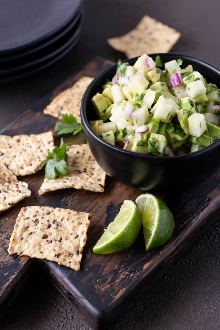Jicama Avocado Salsa in a black bowl surrounded by tortilla chips and fresh lime wedges.