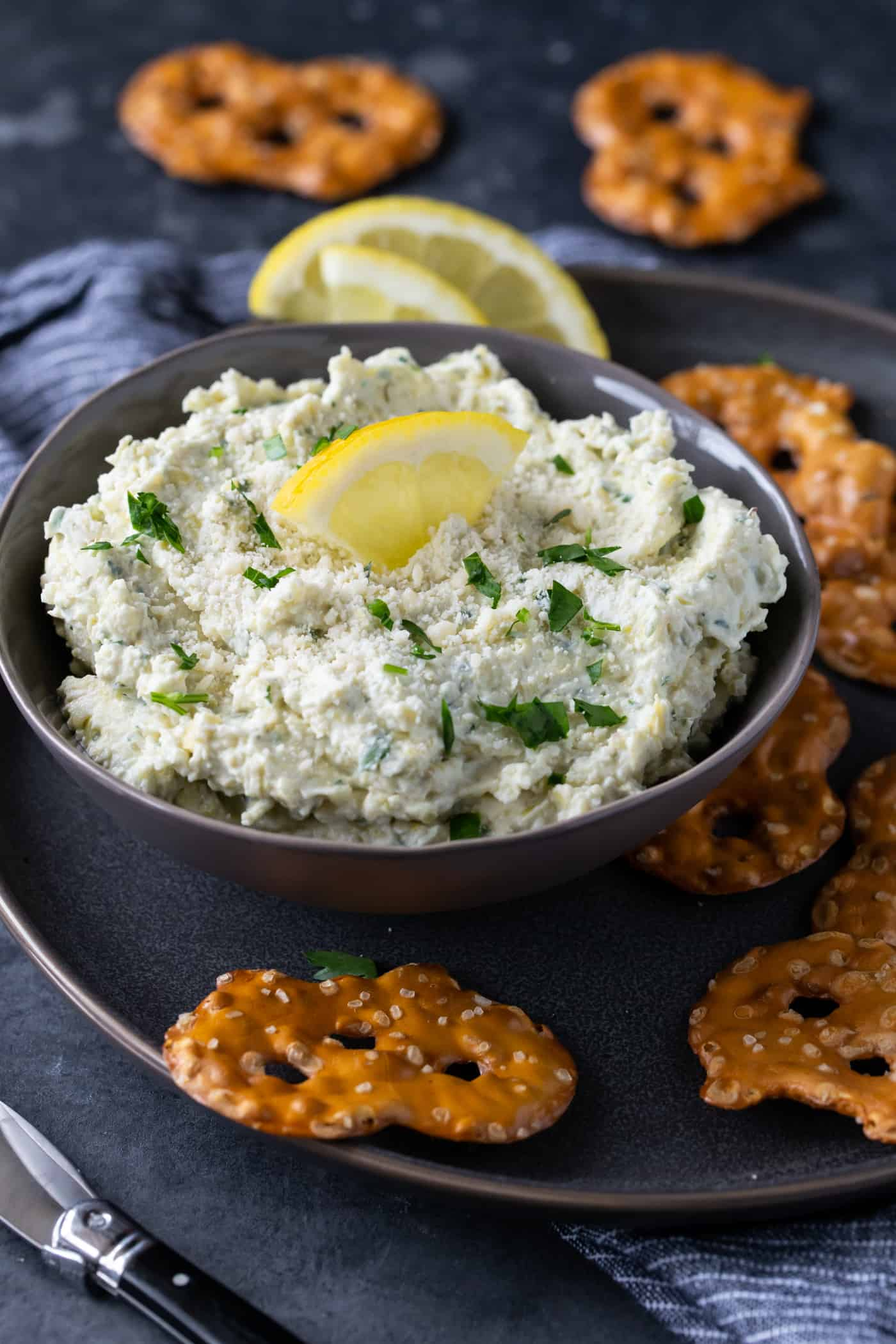 Lemon Artichoke Dip in a gray bowl garnished with fresh parsley and a lemon wedge.