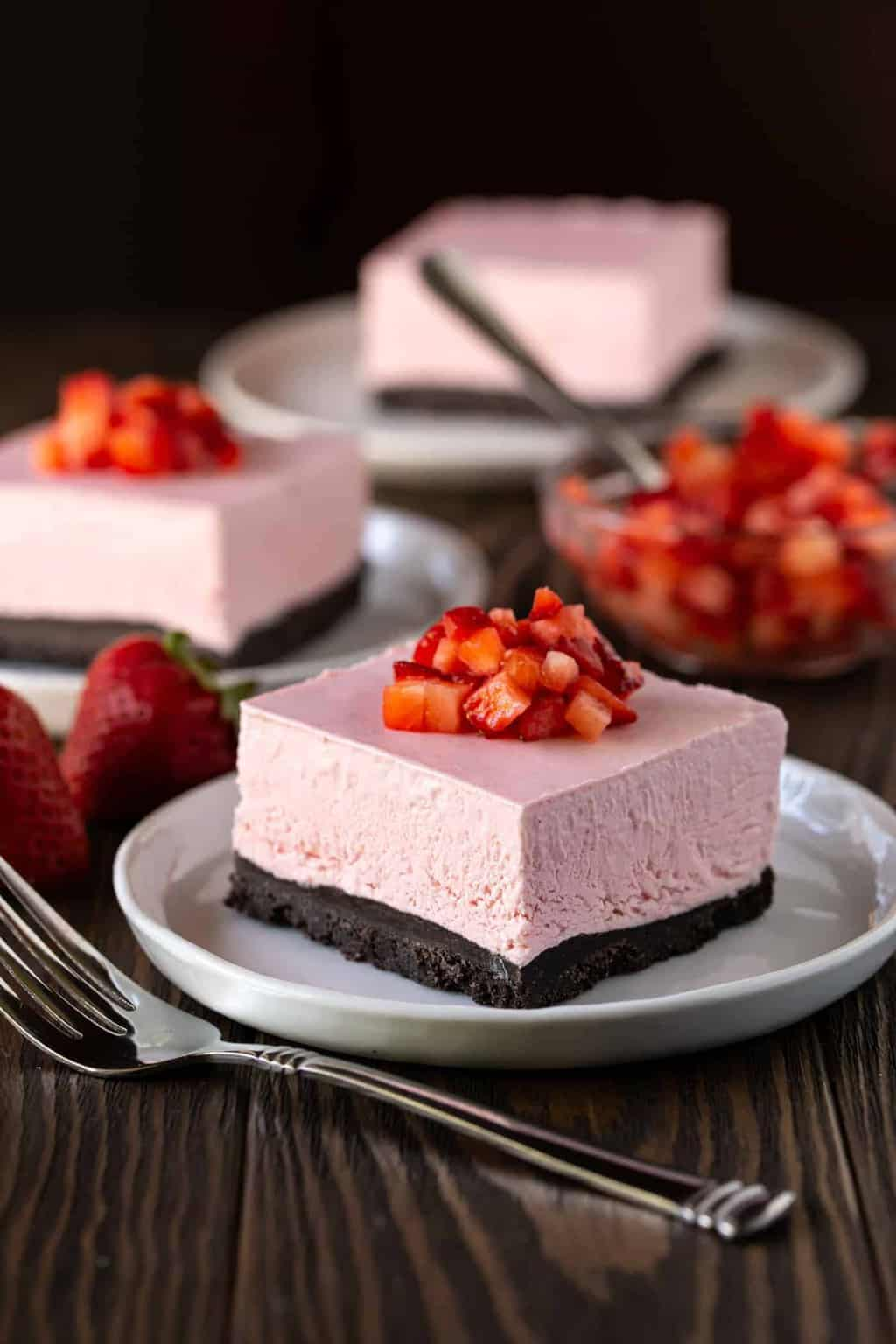 Cut No Bake Strawberry Cheesecake Bar on a gray plate with chopped strawberries on top.