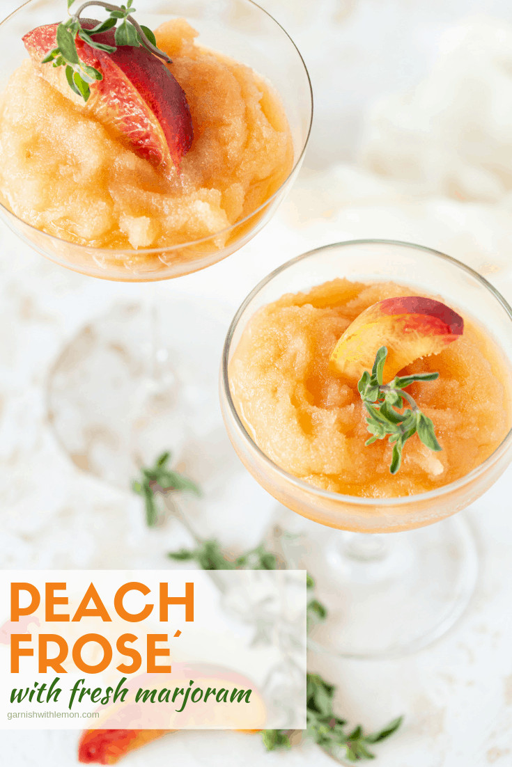 Two coupe cocktail glasses filled with Peach Frosé and garnished with fresh peach wedges and fresh marjoram.