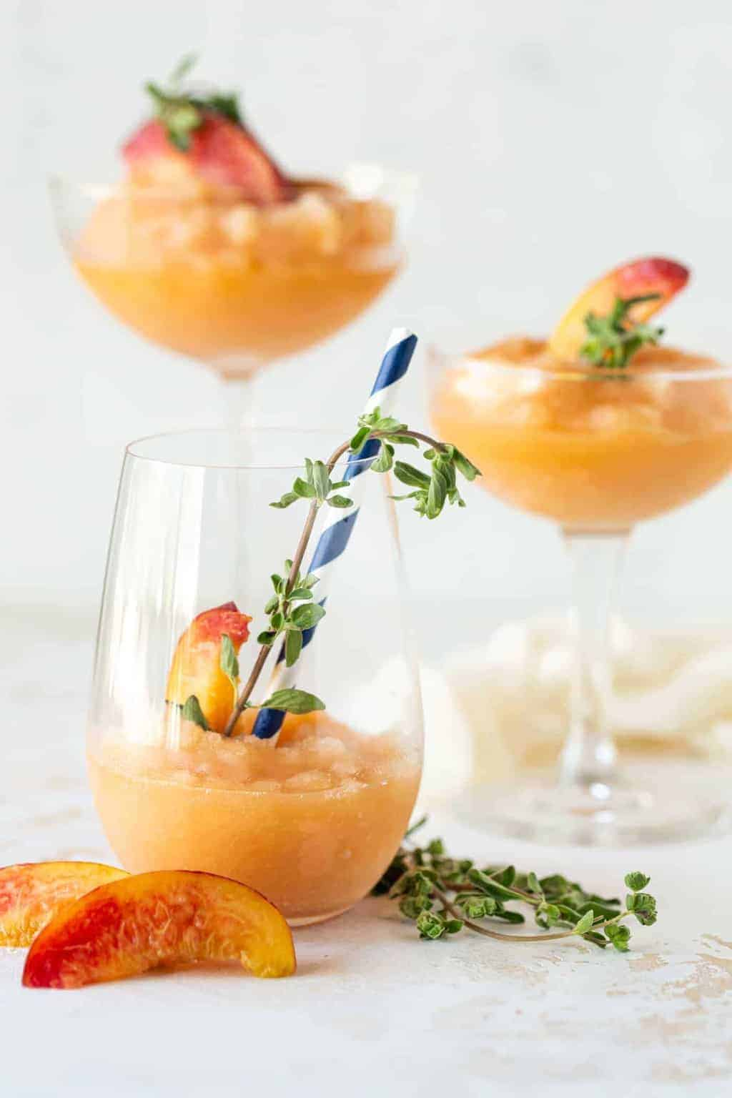 Three different cocktail glasses filled with Peach Frosé and garnished with fresh marjoram and fresh peach wedges.