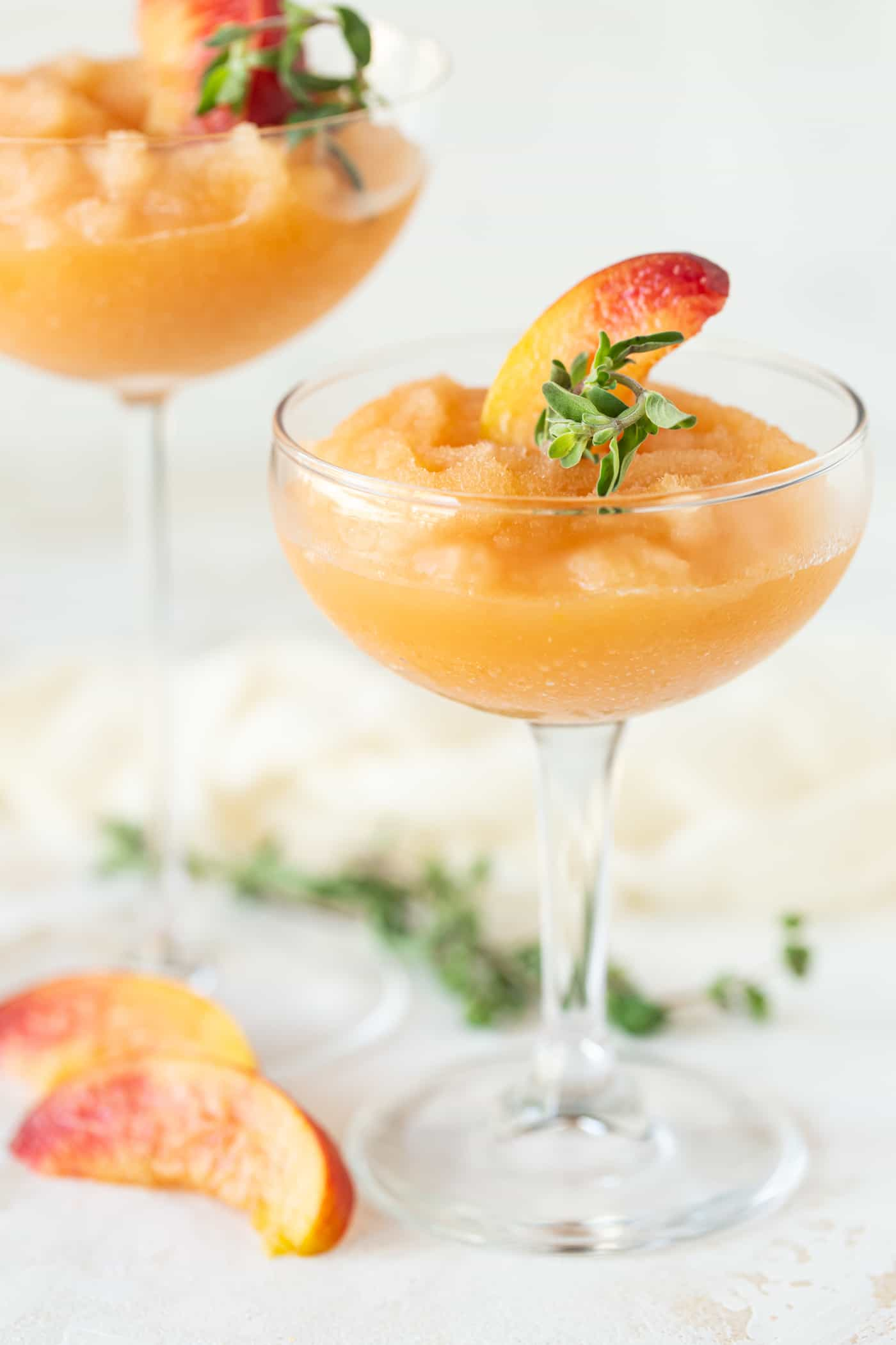 Two coupe cocktail glasses filled with Peach Frosé. Garnished with fresh peach wedges and fresh marjoram.