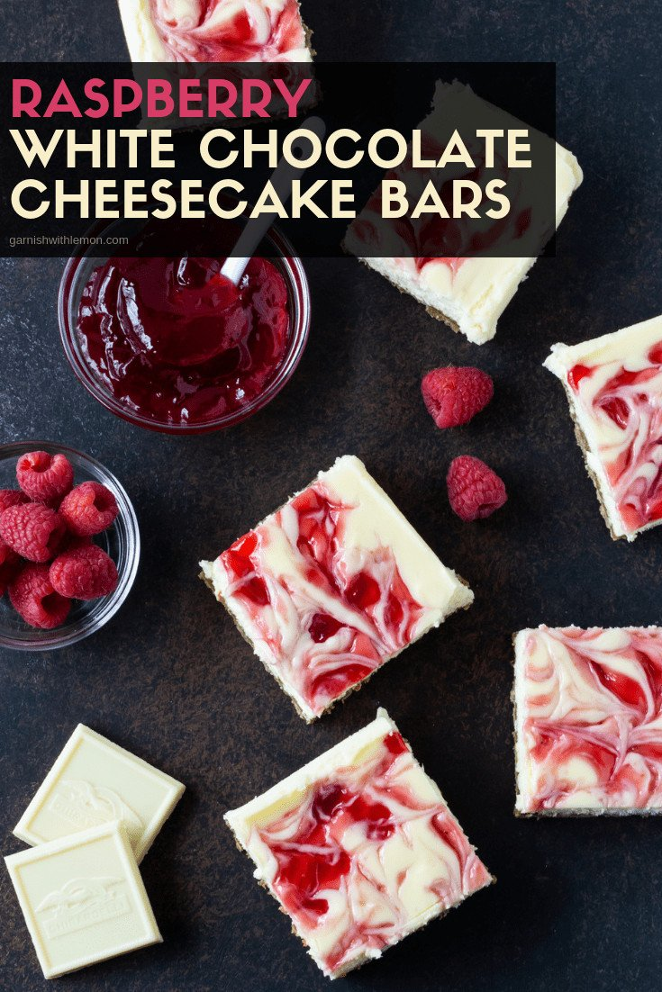 Raspberry White Chocolate Cheesecake bars cut into squares on a dark surface.
