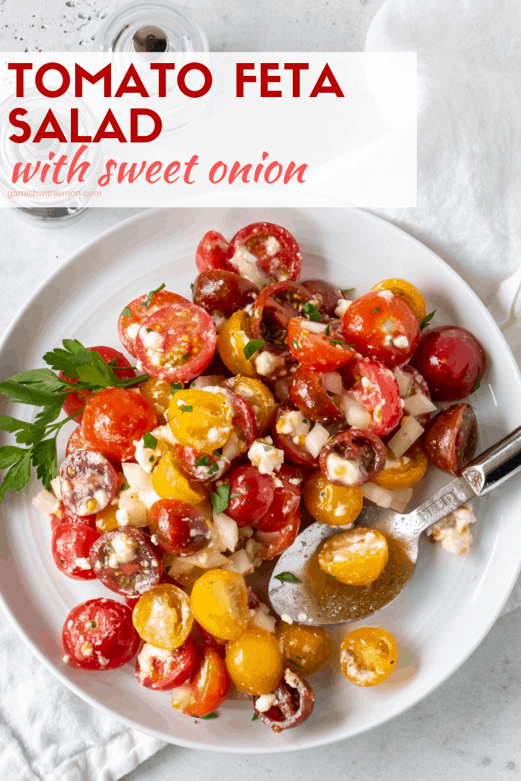 White plate filled with Tomato Feta Salad with Sweet Onion.