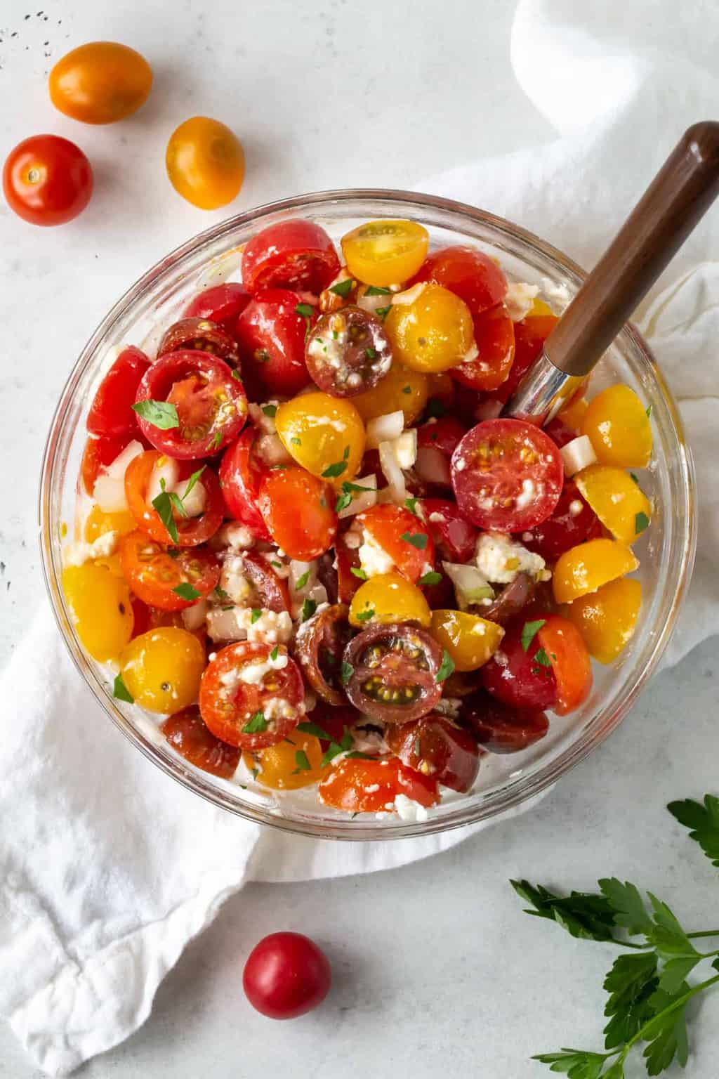 Large glass bowl filled with Tomato Feta Salad with Sweet Onion. Garnished with chopped parsley.