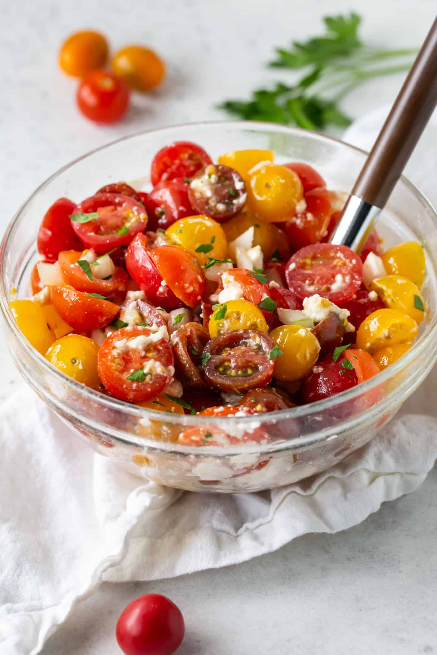 A glass bowl filled with Tomato Feta Salad with Sweet Onion.