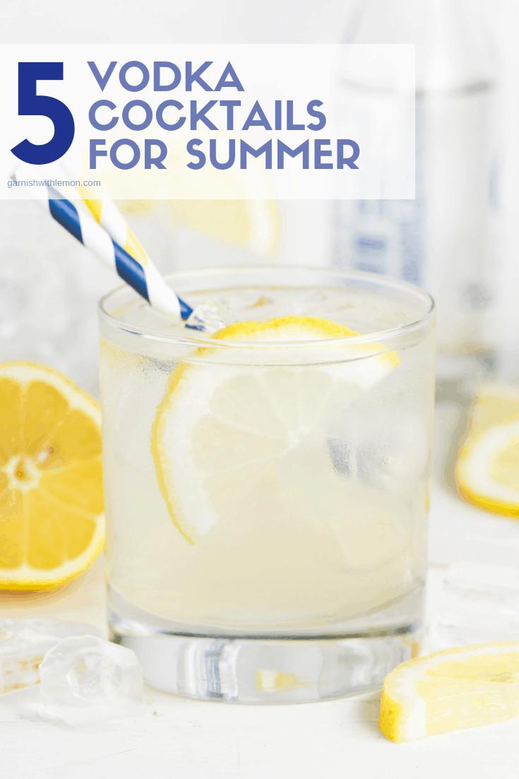Lowball glass of Vodka Elderflower Lemonade garnished with straws and lemon slices.