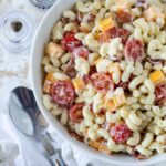bacon ranch pasta salad in a white bowl on a white surface with a spoon for serving.