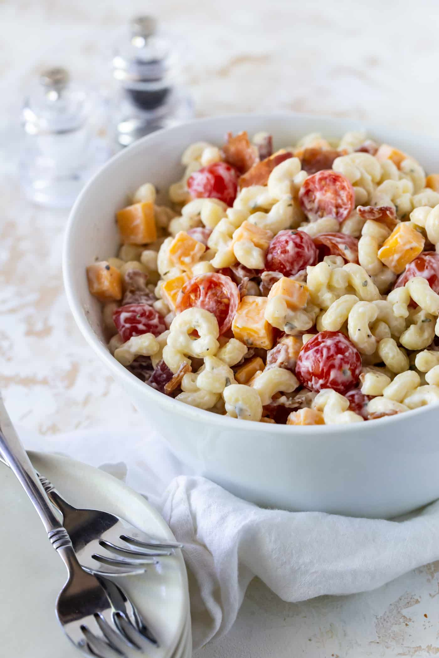 A bowl of pasta with tomatoes, cheese and bacon.