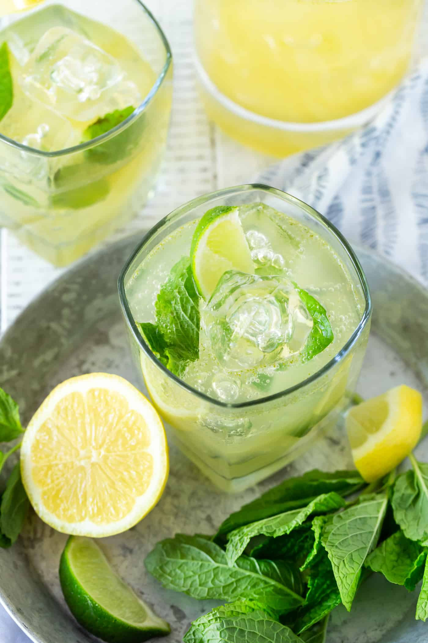 Top dowm image of Bootleg cocktails in a silver tray with lemon wedge, mint leaves and lime slices for garnish.