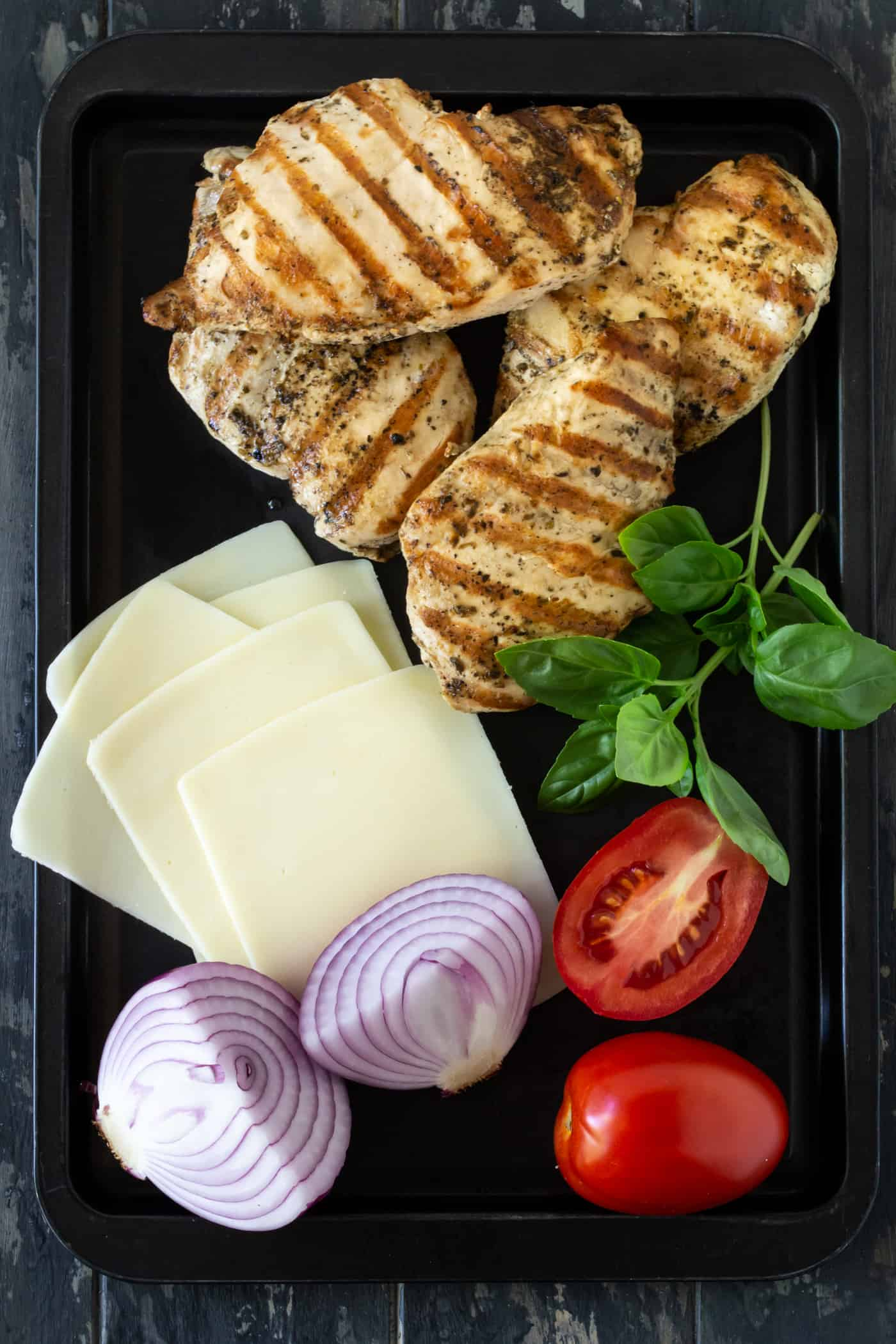 Black platter filled with ingredients for Cheesy Grilled Bruschetta Chicken