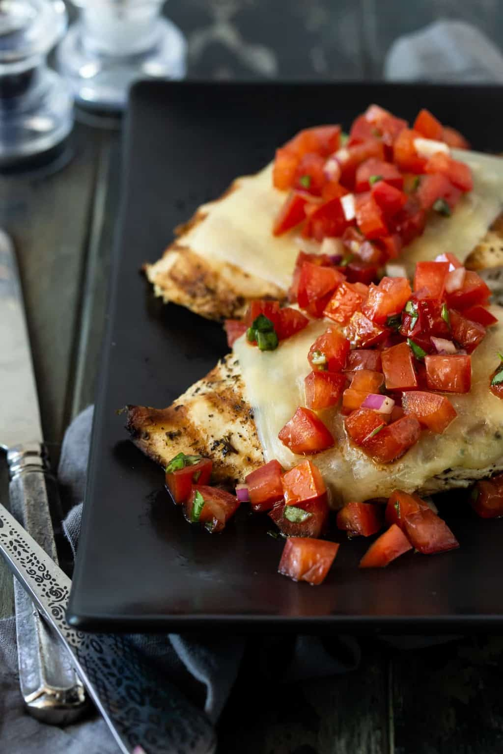 Two pieces of easy Cheesy Grilled Chicken Bruschetta on a black plate. Topped with melted mozzarella cheese and fresh tomato bruschetta topping.