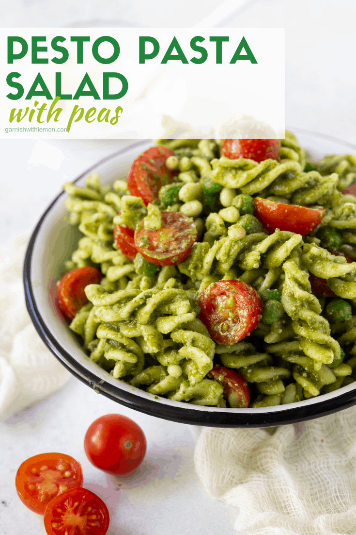 Pesto Pasta salad mounded in small white bowl with black trim. Garnished with fresh tomatoes and parmesan cheese.