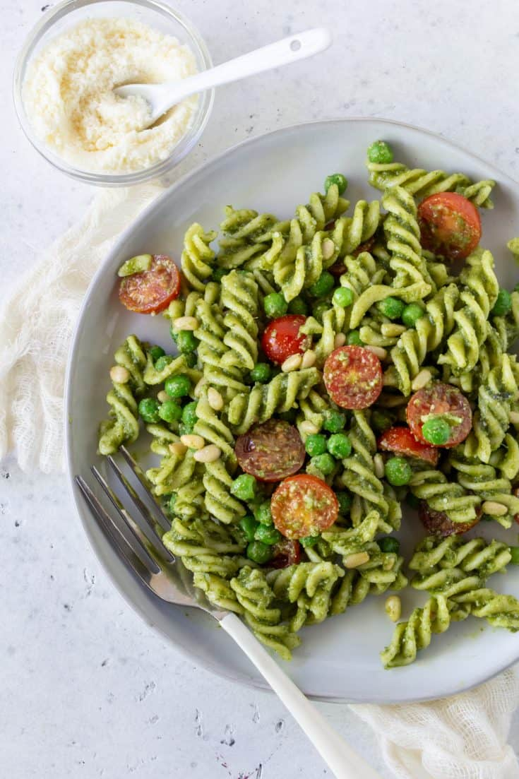 Top down image of Pesto Pasta salad with tomateos and peas on a white plate with a bowl of parmesan cheese on the side.