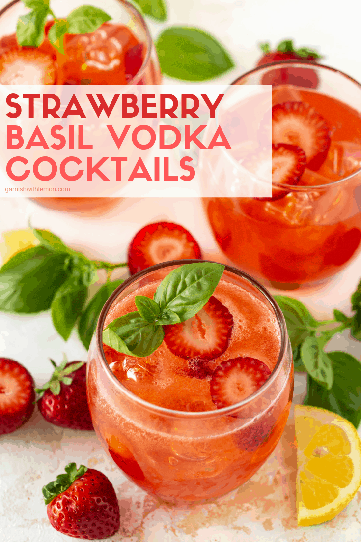 Three lowball glasses filled with ice and Strawberry Basil Vodka Cocktails. Garnished with fresh strawberry slices and basil leaves.