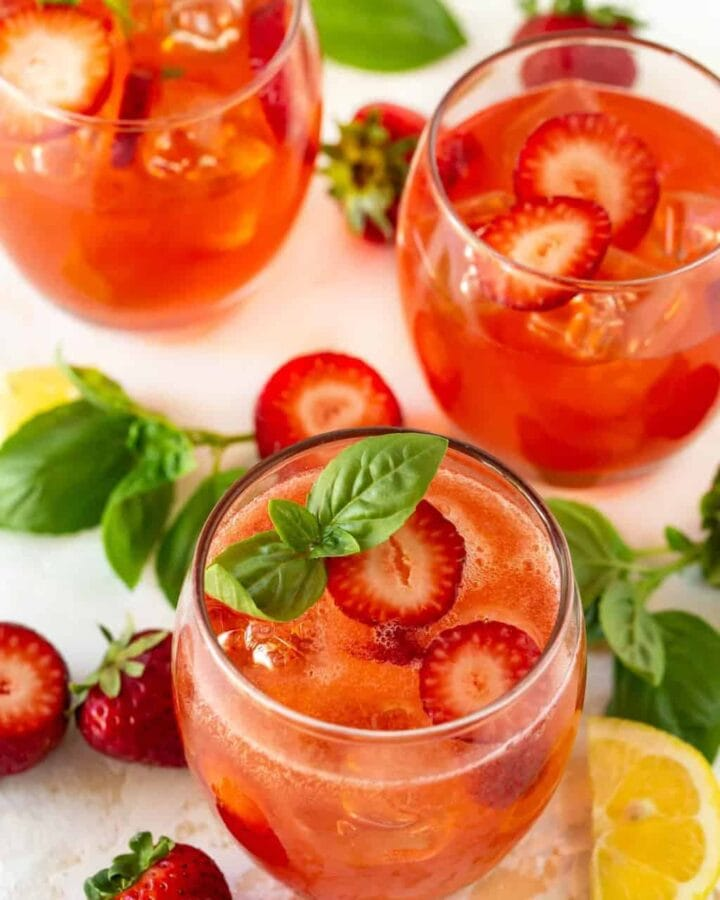 Three lowball glasses filled with Strawberry Basil Vodka Cocktails. Garnished with fresh strawberries, fresh basil and lemon wedges.