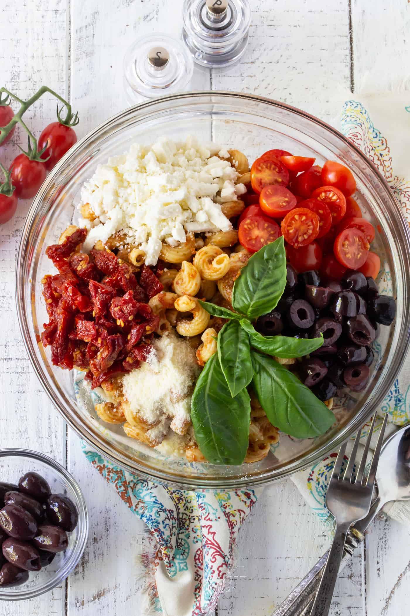 Glass bowl filled with pasta, kalamata olives, feta cheese and sun dried tomatoes.