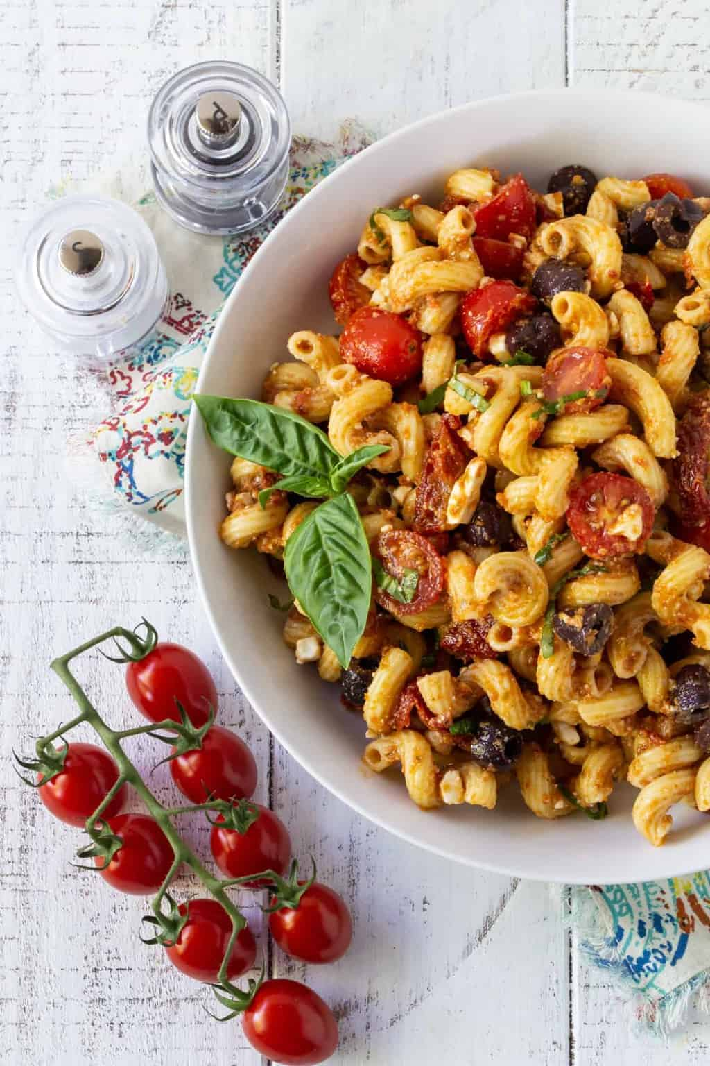 Pasta Salad in a white bowl with cherry tomatoes and fresh basil.