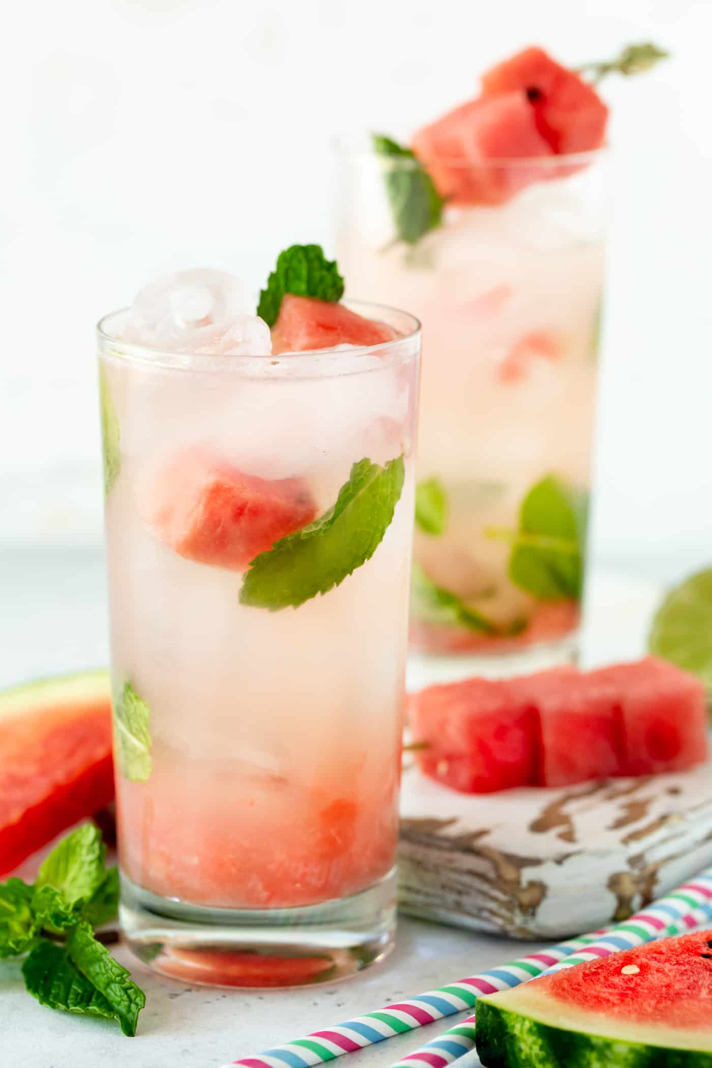 Two highball glasses on a white board filled with ice and Watermelon Mojitos. Garnished with fresh mint leaves and watermelon chunks.