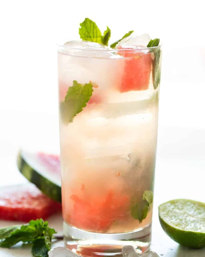 A single highball glass filled with ice and a watermelon mojito cocktail. Garnished with fresh watermelon and mint leaves.