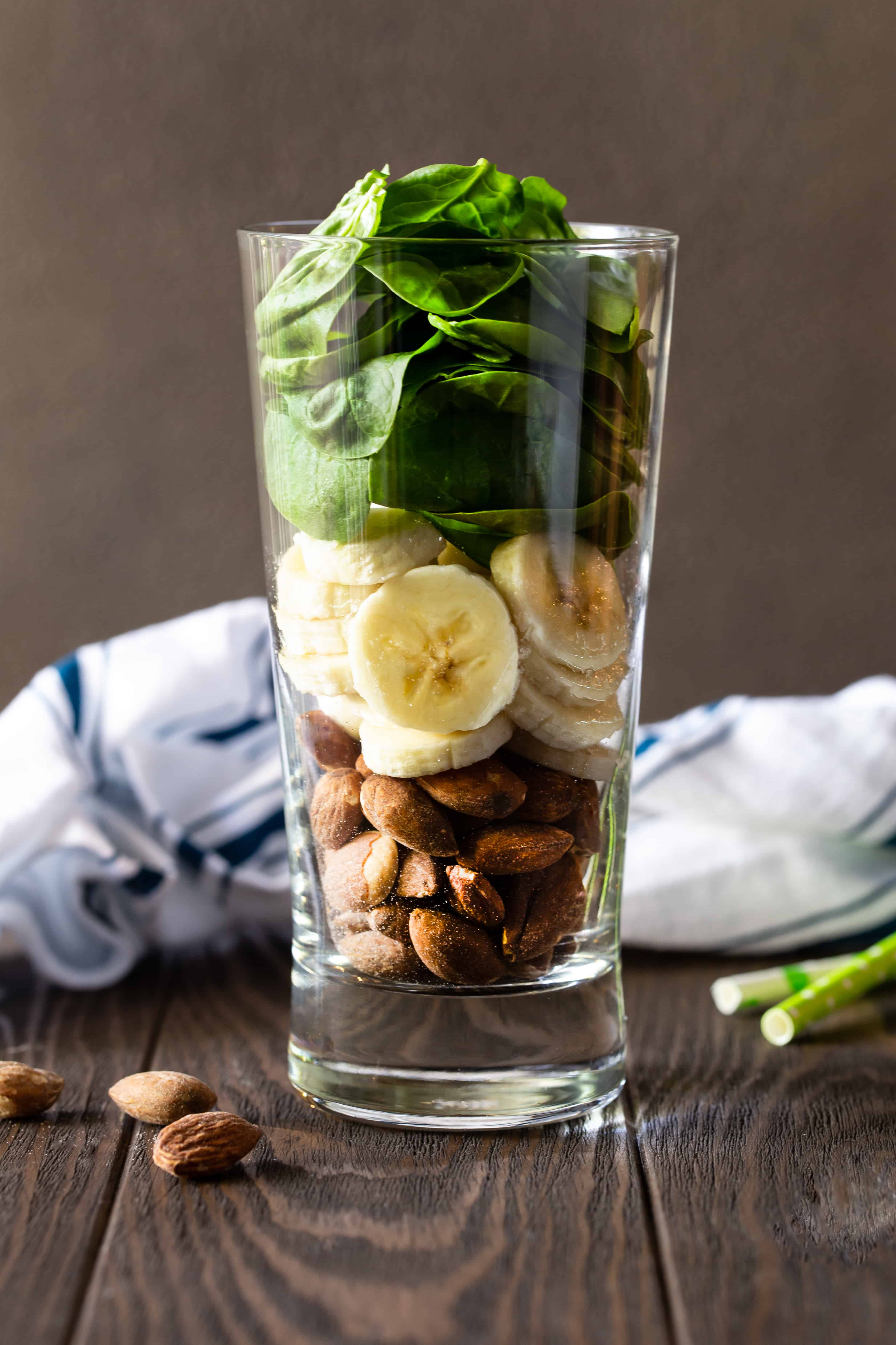 Glass filled with ingredients of Banana Spinach Protein Smoothie, including fresh spinach, banana slices and almonds.