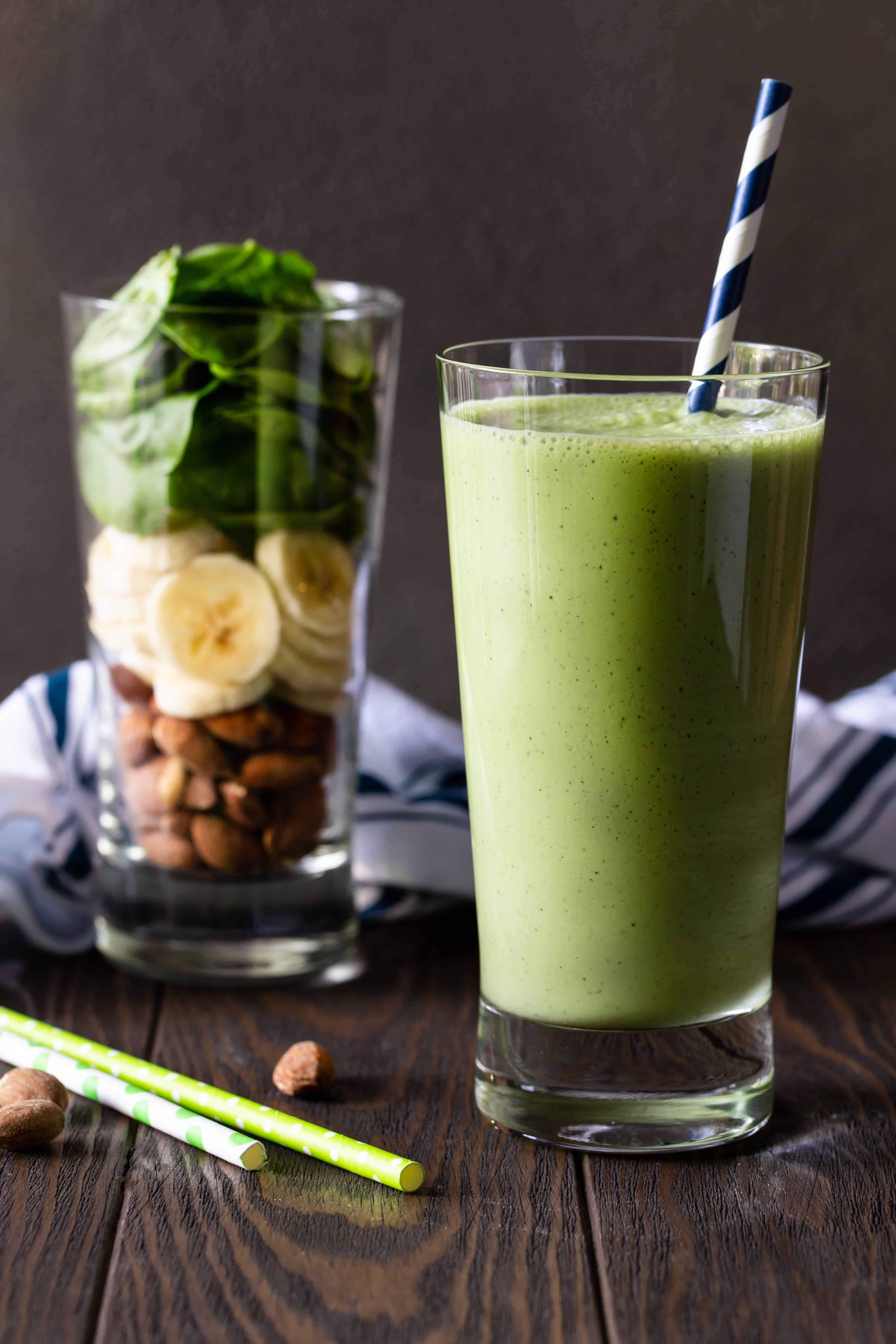 Two glasses on a wood board. One is filled with raw ingredients for smoothie and other is filled with blended Banana Spinach Protein Smoothie.